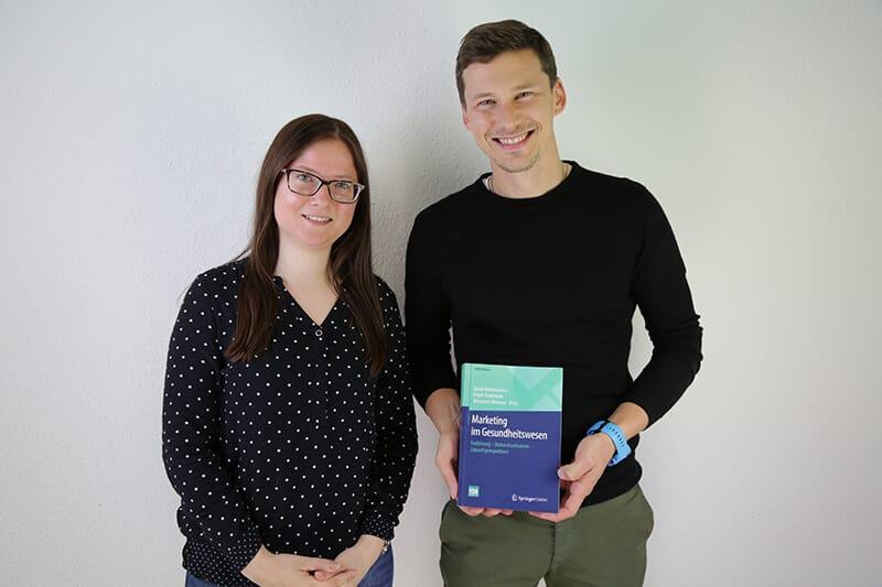 """Bild von zwei xeomed-Mitarbeitern mit Buch """"Marketing im Gesundheitswesen""""."""
